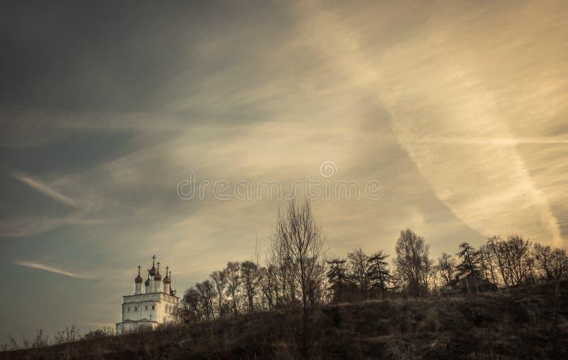 El paisaje rural dramático del campo con la iglesia en la colina y el cielo dramático de la puesta del sol copian el espacio imagen de archivo libre de regalías