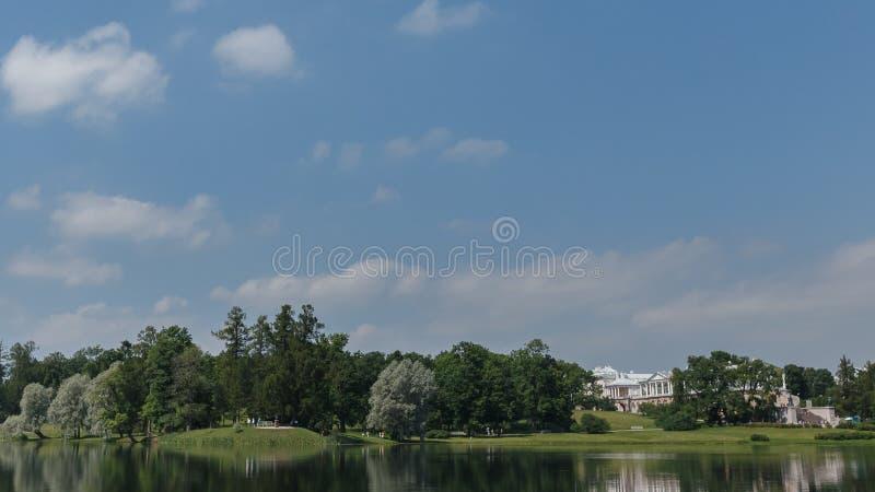 El paisaje ruso hermoso con los sauces acerca al agua de un lago y a las nubes en cielo azul imagen de archivo libre de regalías