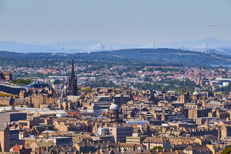 El paisaje urbano de Edimburgo con las iglesias, adelante tiende un puente sobre y puente de Queensferry en el fondo fotos de archivo libres de regalías