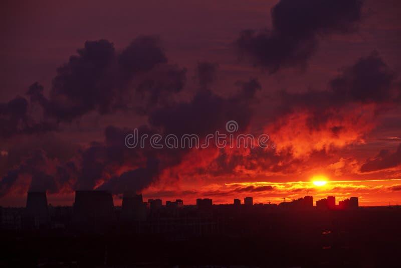 El paisaje urbano en la puesta del sol, chimeneas de la fábrica fuma, paisaje industrial, noche, puesta del sol sobre la ciudad fotos de archivo