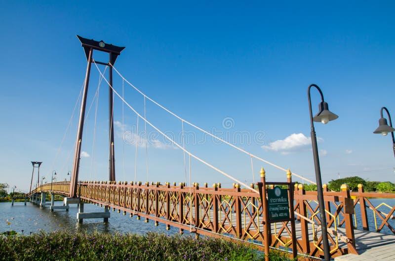 El palmo de madera de puente colgante que a través del pequeño lago en Wareepirom parquea fotografía de archivo
