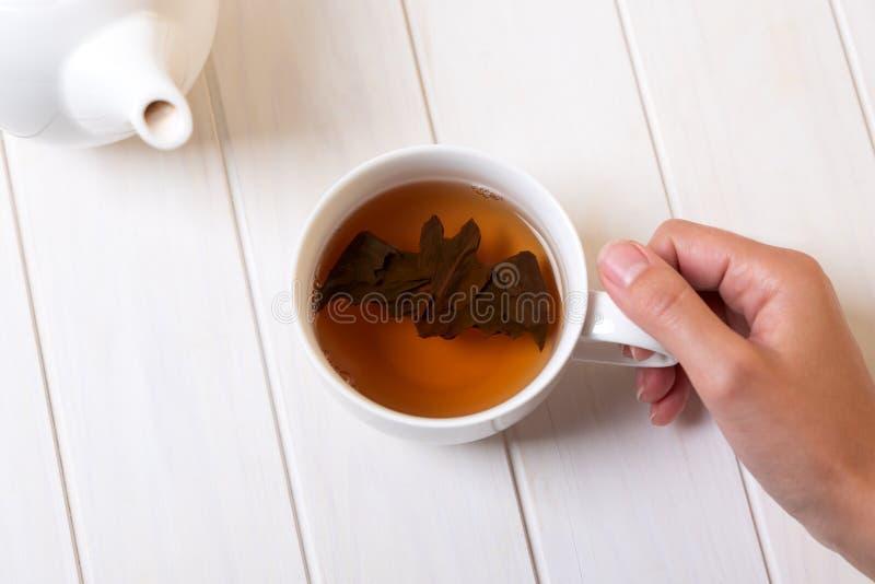 El palo de Halloween hace de las hojas de té en la taza de té en la tabla de madera blanca Concepto de la celebraci?n de Hallowee imagenes de archivo