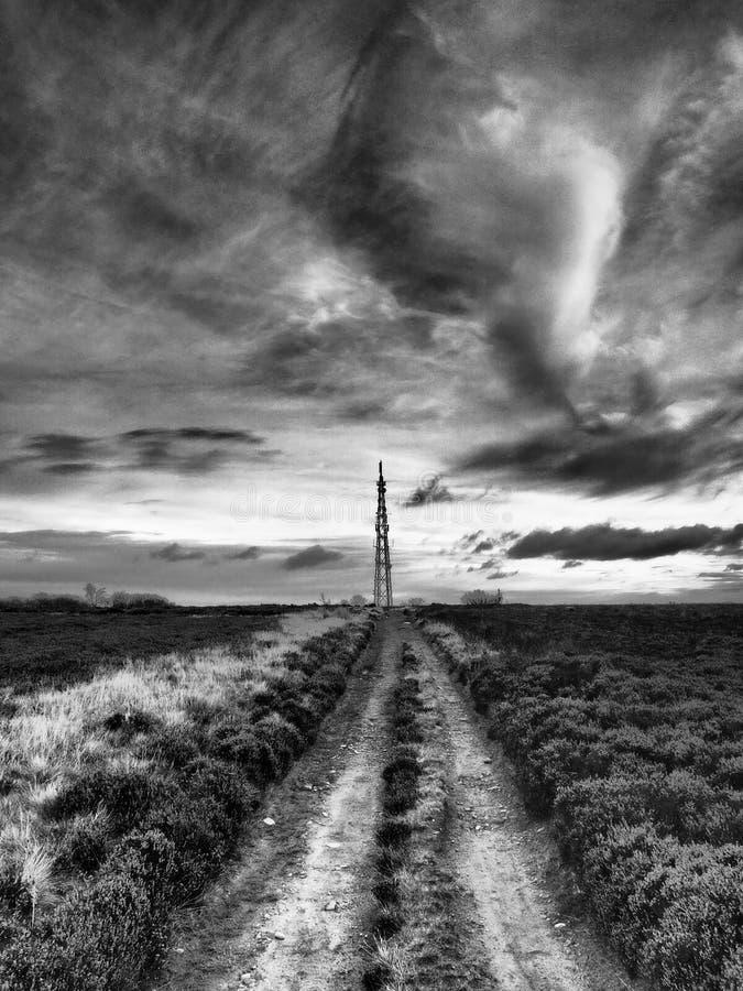 El palo del transmisor visto de Howdale amarra debajo del cielo oscuro del empollamiento que amenaza imagenes de archivo