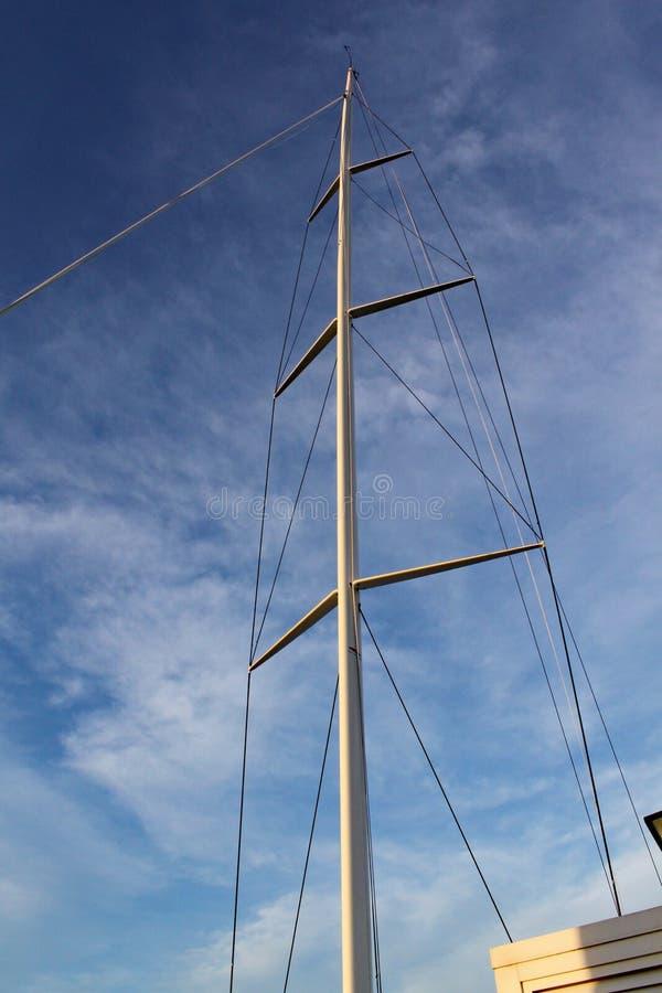 El palo y el aparejo de un yate que compite con se destaca contra el cielo azul claro fotografía de archivo