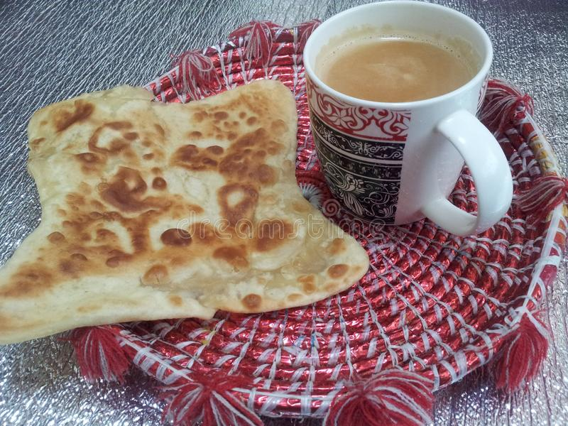 El pan aceitoso de Paratha con la taza de té sirvió en changair foto de archivo libre de regalías