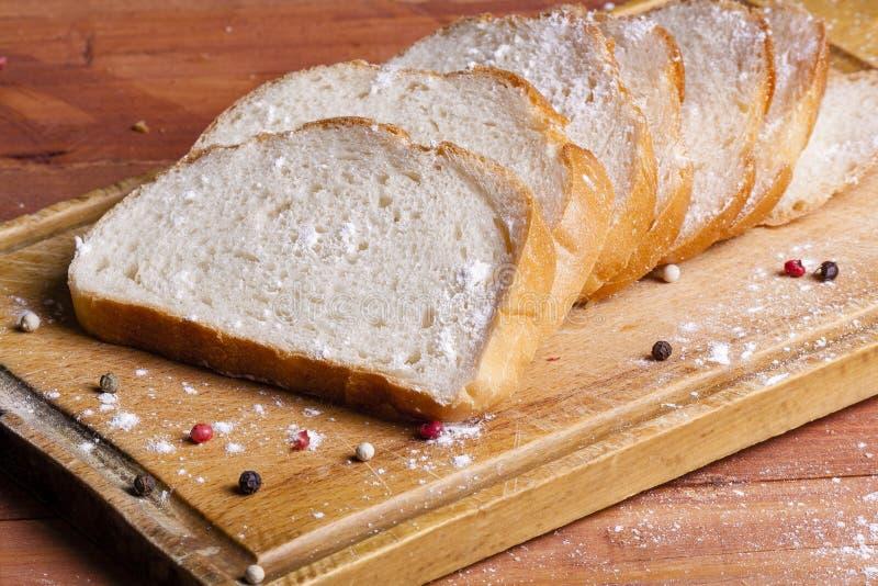 El pan blanco fresco y fragante es cortado y de mentira en un b de madera foto de archivo