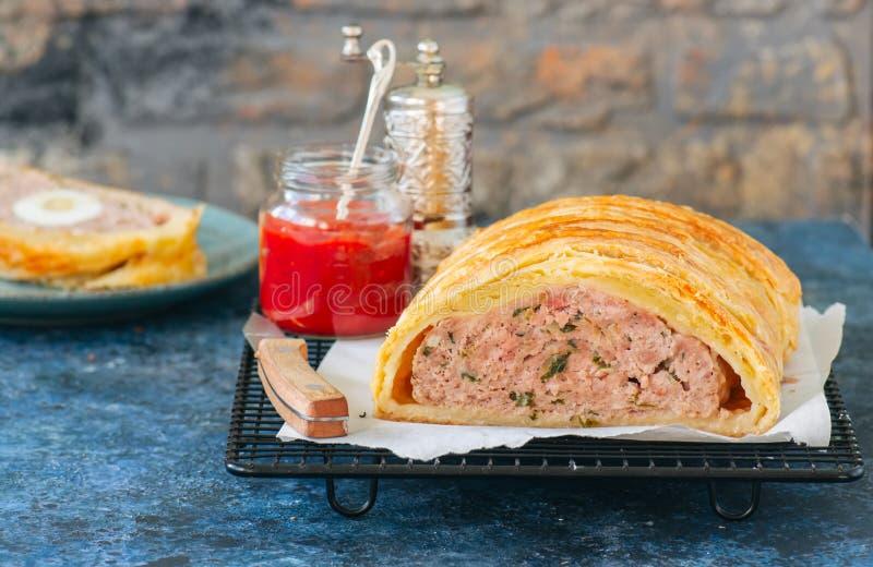 El pan con carne de Turquía en una pasta de hojaldre sirvió en un estante de rejilla Sto azul fotos de archivo libres de regalías