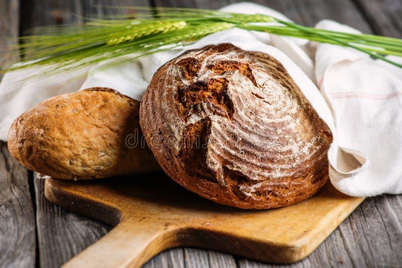 El pan de Rye con los granos en la tabla de cortar el pan de madera, fondo de la comida, coció recientemente el pan tradicional imagen de archivo