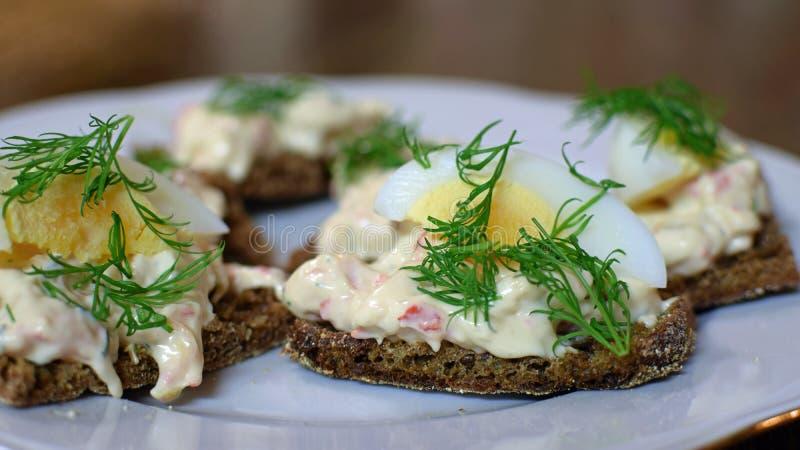 El pan de Rye remató el huevo hervido, el eneldo y la crema batida con los cangrejos europeos fotos de archivo