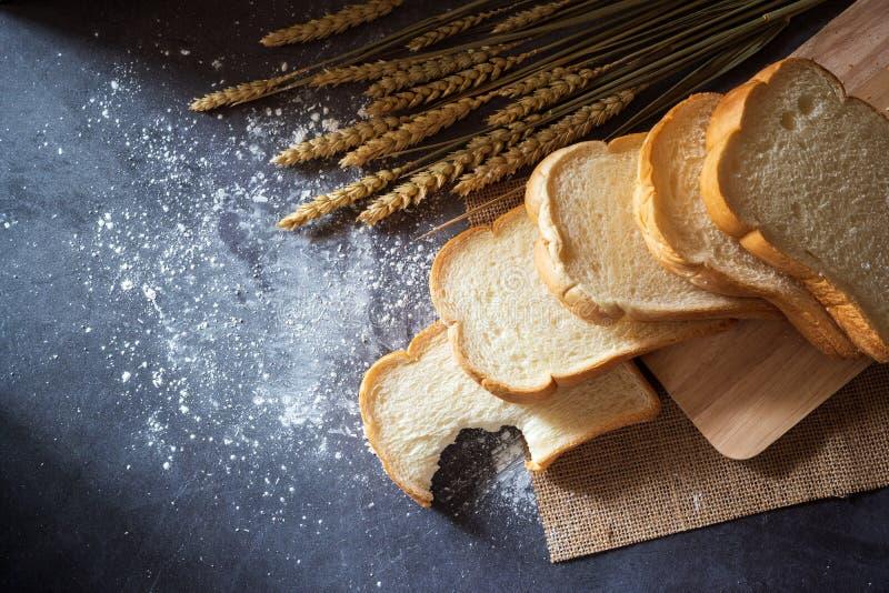El pan en una tabla de cortar de madera y los granos del trigo colocados por otra parte con la harina de trigo dispersaron imagen de archivo