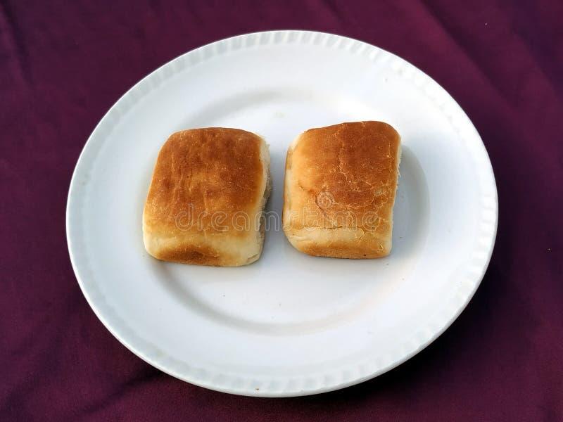 El pan, icono de la panader?a, cort? el pan fresco del trigo en el fondo blanco fotografía de archivo