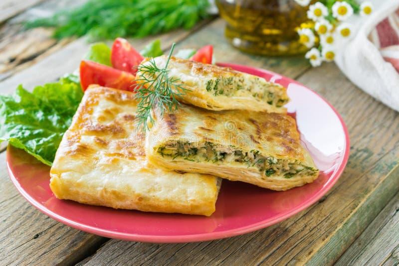 El pan Pita frito relleno con el pollo, el queso e hierbas sirvió en una placa de cerámica Fondo de madera Foco selectivo foto de archivo