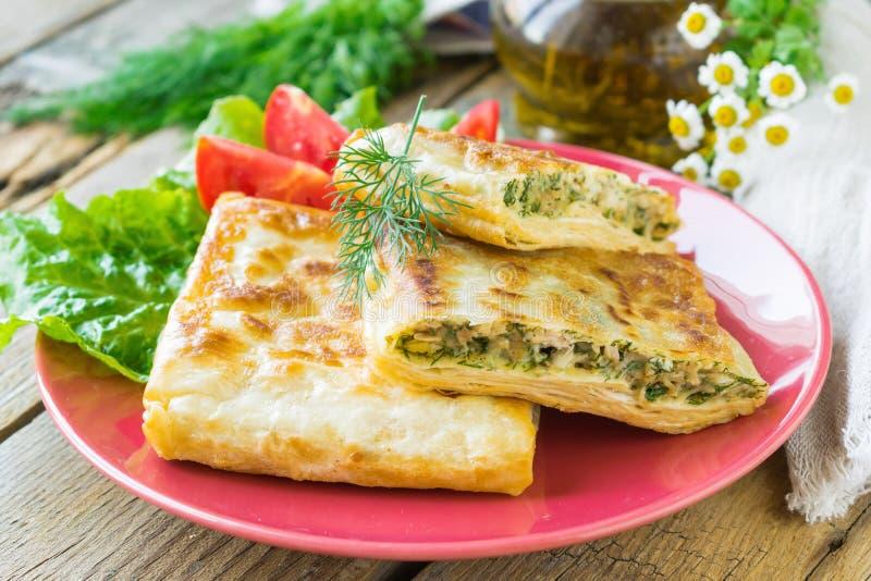 El pan Pita frito relleno con el pollo, el queso e hierbas sirvió en una placa de cerámica Fondo de madera Foco selectivo foto de archivo libre de regalías