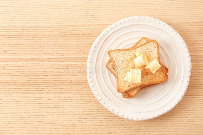 El pan tostado con mantequilla se encrespa en la placa fotografía de archivo