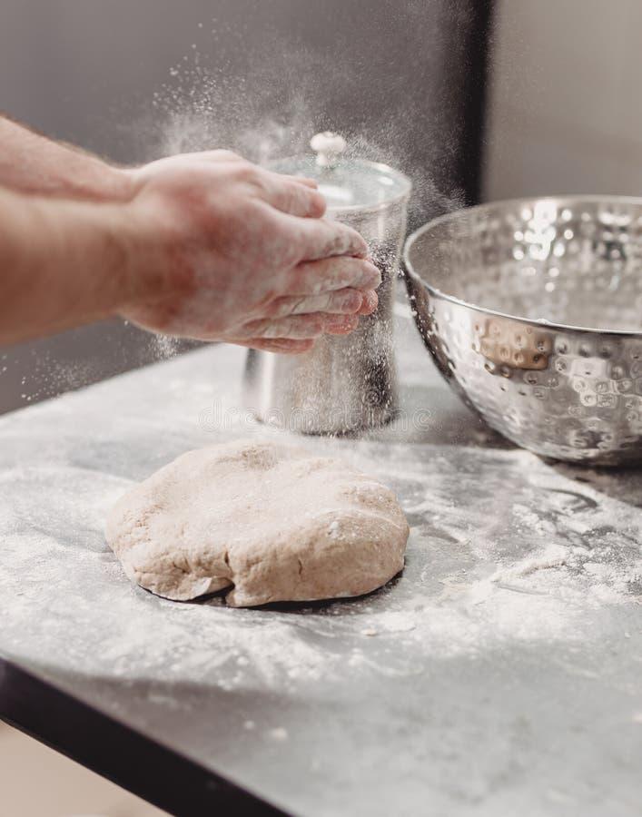 El panadero añade la harina a la pasta en la tabla en la panadería fotografía de archivo libre de regalías