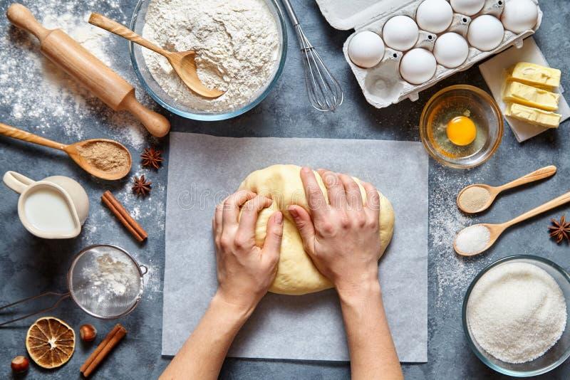 El panadero amasa ingridients de la receta del pan, de la pizza o de la empanada de la pasta con las manos, endecha del plano de  foto de archivo libre de regalías