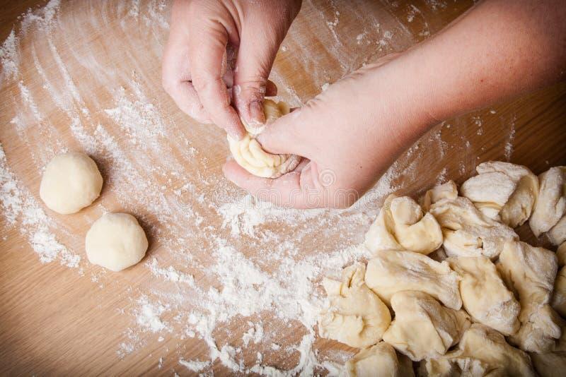 El panadero amasa la pasta cruda en una tabla de madera foto de archivo