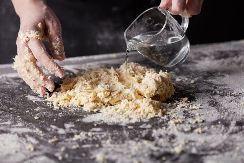 El panadero amasa la pasta para cocer en una tabla de cocina oscura foto de archivo libre de regalías