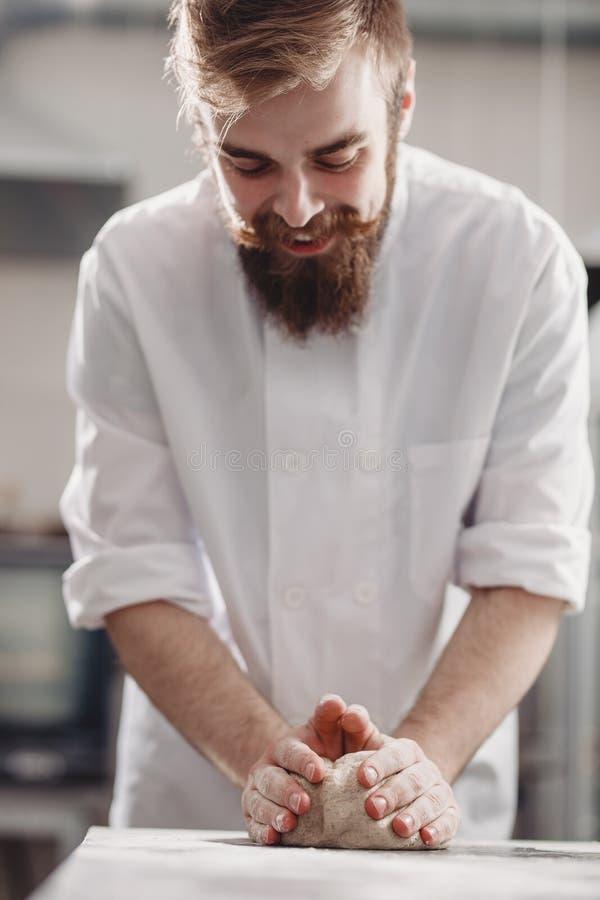 El panadero carismático con una barba y un bigote amasa la pasta en la tabla en la panadería fotografía de archivo
