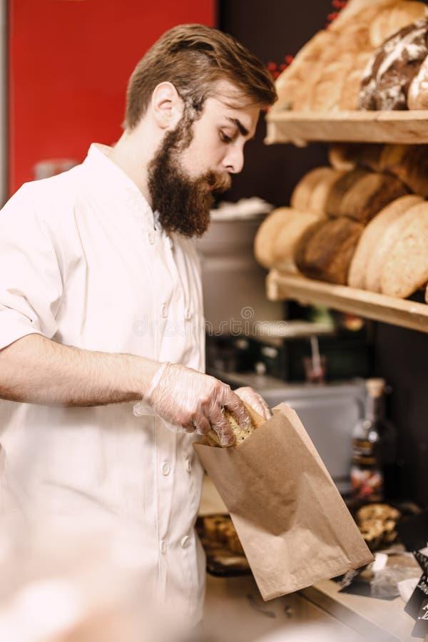 El panadero carismático con una barba y un bigote pone el pan fresco en una bolsa de papel en la panadería imagen de archivo libre de regalías