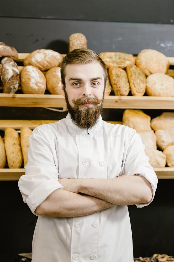 El panadero carismático se coloca en el fondo de estantes con pan fresco en la panadería foto de archivo libre de regalías