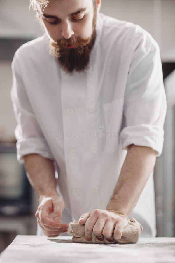 El panadero carism?tico con una barba y un bigote amasa la pasta en la tabla en la panader?a foto de archivo