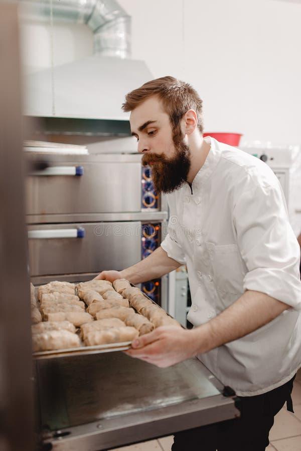 El panadero carism?tico joven pone una bandeja que cuece con los rollos de panes en el horno en la panader?a imagen de archivo