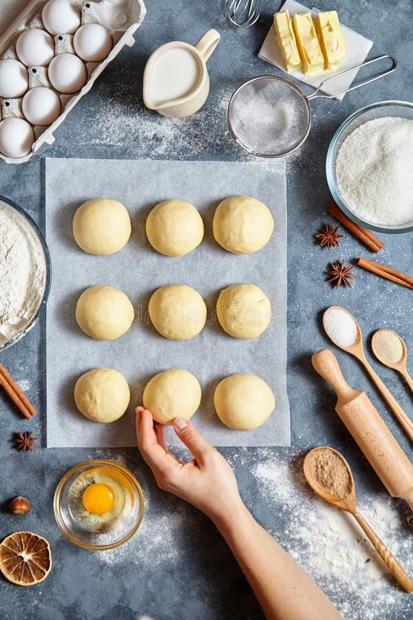 El panadero da la preparación de la pasta para la endecha plana de la comida de los ingridients de los bollos en la tabla de coci fotos de archivo libres de regalías