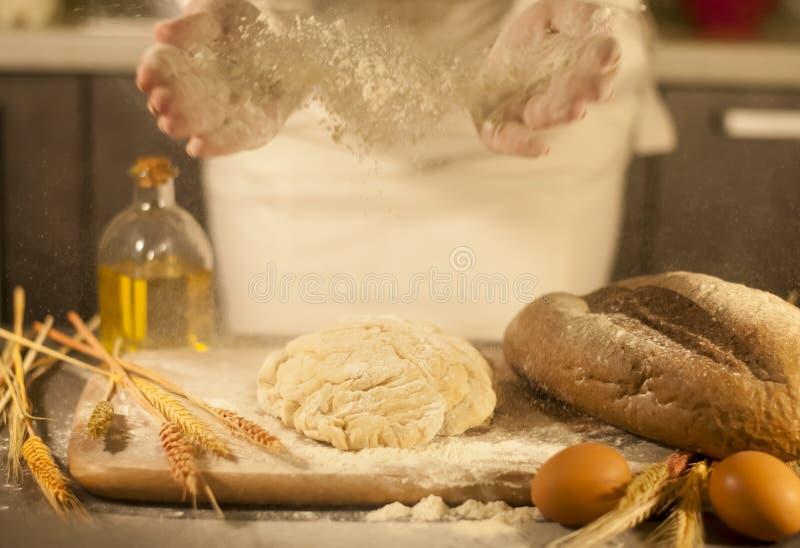 El panadero de la mujer da, amasa la pasta y pan de la fabricación, mantequilla, harina del tomate foto de archivo