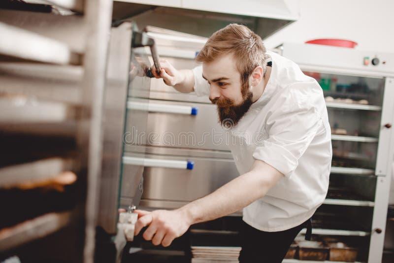 El panadero mira a escondidas en el horno y regula la temperatura de la hornada en la panadería foto de archivo libre de regalías