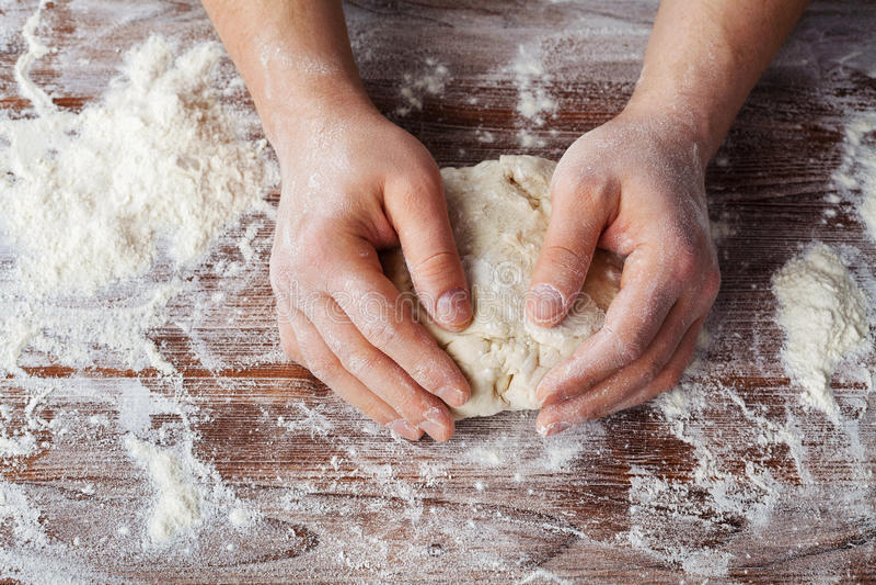 El panadero prepara la pasta en una tabla de madera, las manos masculinas amasa la pasta con la harina foto de archivo libre de regalías