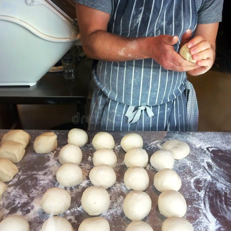 El panadero prepara los rollos de pan fotos de archivo