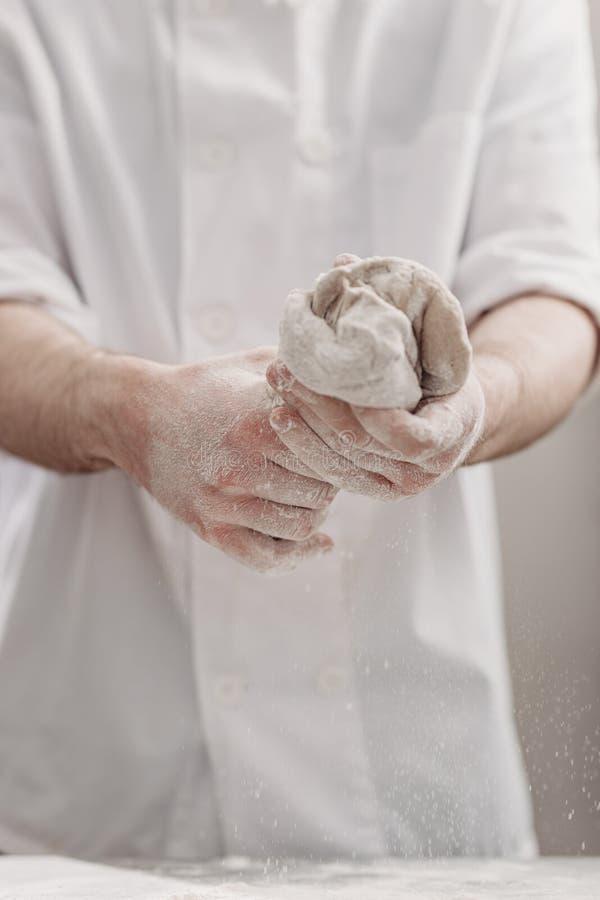 El panadero profesional amasa la pasta en sus manos en la cocina de la panader?a fotos de archivo libres de regalías
