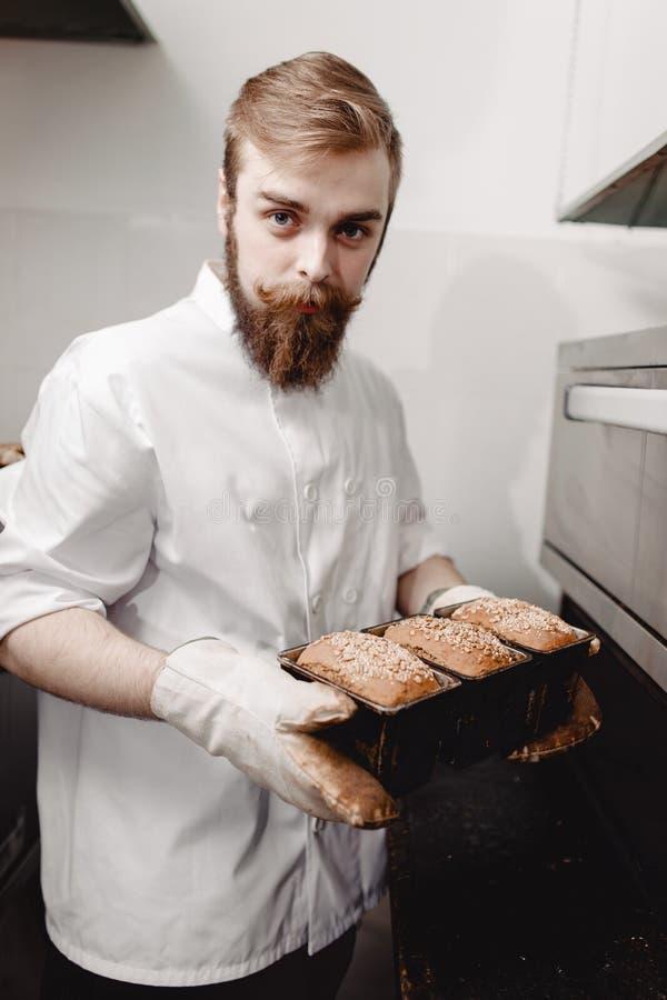El panadero saca del horno un molde para el horno la bandeja que cuece con los panes del pan nuevo-cocidos en la panadería fotografía de archivo libre de regalías
