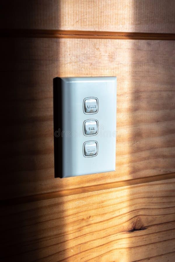 El panel blanco del interruptor de la luz en una pared de madera foto de archivo