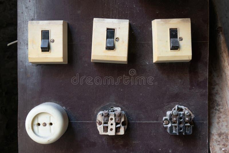 El panel con los interruptores eléctricos y los zócalos eléctricos quebrados foto de archivo