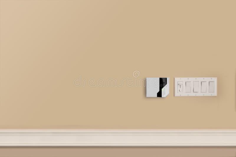 El panel de alarma e interruptores ligeros en una pared amarillenta foto de archivo