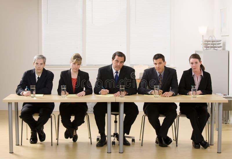 El panel de los compañeros de trabajo alrededor para conducir una entrevista fotografía de archivo libre de regalías