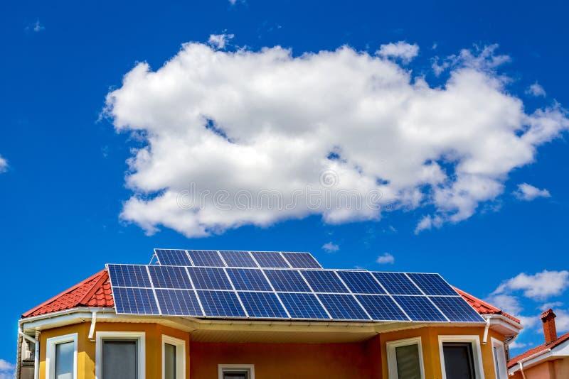 El panel solar en un tejado rojo que refleja el sol y el cielo azul imagenes de archivo