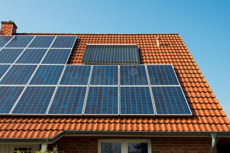 El panel solar en una azotea roja fotografía de archivo