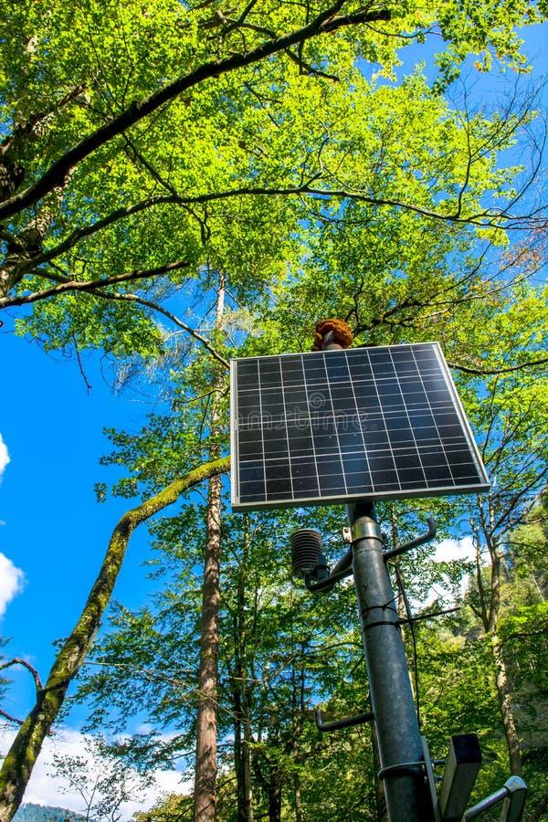 El panel solar iluminado por el sol en el bosque fotografía de archivo libre de regalías