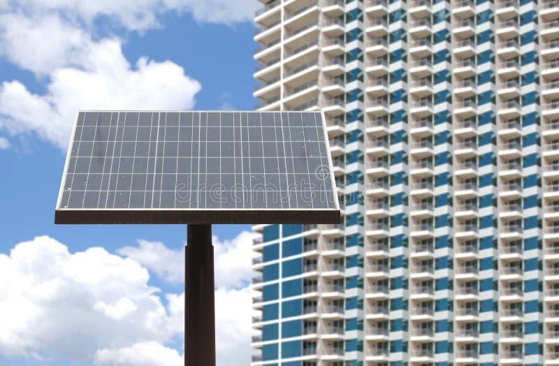 el panel solar y alto fondo del edificio fotografía de archivo libre de regalías