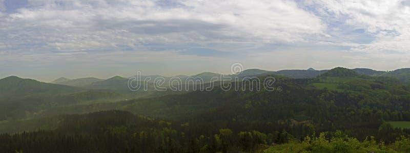 El panorama amplio de las montañas hory de Luzicke, la opinión del horizonte del vrch del stredni de la colina, el bosque verde y fotografía de archivo