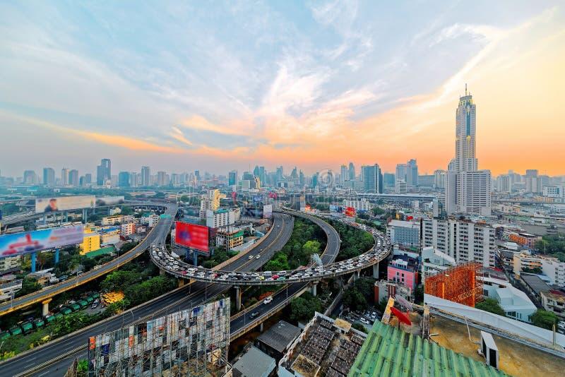 El panorama de Bangkok en la oscuridad con los rascacielos en fondo y tráfico se arrastra en las autopistas elevadas y los interc foto de archivo