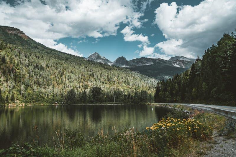 El panorama de la montaña con la reflexión florece el cielo azul y las nubes, Columbia Británica, Canadá imagen de archivo