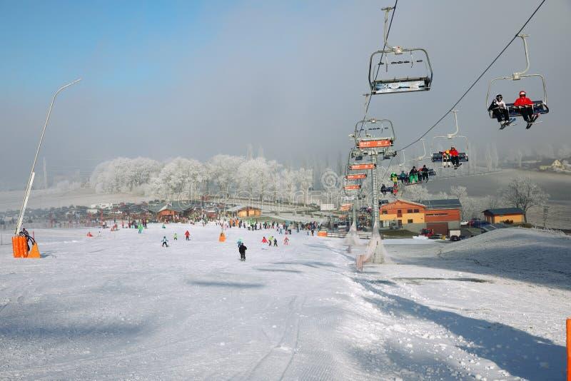 El panorama de las montañas del invierno con las cuestas y los remontes del esquí, el día soleado con niebla y el sol irradia imagenes de archivo