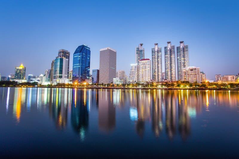El panorama del paisaje urbano con los rascacielos y el cielo alinean por noche del parque de Benjakitti en Bangkok, Tailandia imagen de archivo libre de regalías