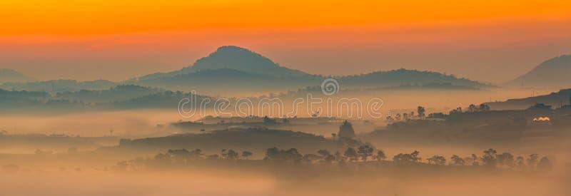 El panorama hermoso de la mañana ajardina con la niebla a través de las montañas imagenes de archivo