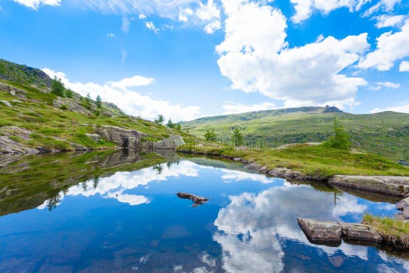 El panorama italiano de la montaña, nubes reflejó en el lago alpino foto de archivo