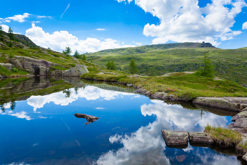 El panorama italiano de la montaña, nubes reflejó en el lago alpino imagenes de archivo